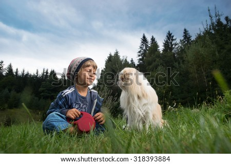 Cute little boy sitting in the meadow smiling at his dog  Best friends concept. - stock photo