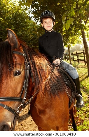 Cute little boy sitting on horseback in nature, smiling.