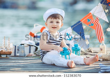 cute little boy sitting on the floor on pier outdoor, a marine style. Little sailor - stock photo