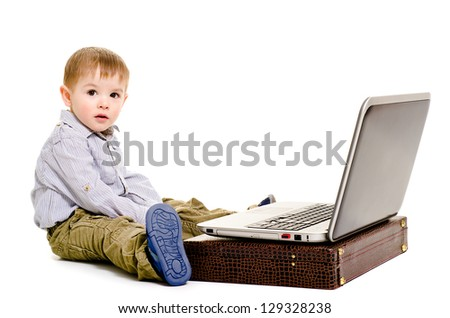Cute little boy sitting on the floor with a laptop - stock photo