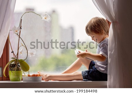 Cute little boy, sitting on the window, playing on tablet - stock photo