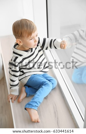 Cute little boy sitting on windowsill