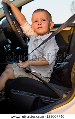 Cute little boy sitting strapped into the safety belt in the drivers seat of a car with his hand on the steering wheel looking at the camera - stock photo
