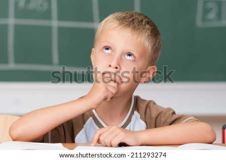 Cute little boy sitting thinking in class at his desk staring up into the air with his hand to his chin as he seeks an answer
