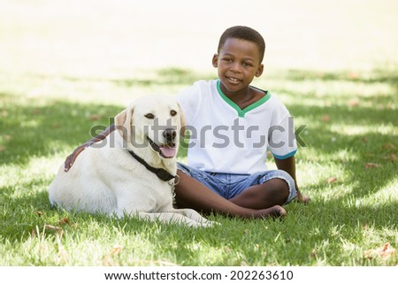 Cute little boy sitting with labrador dog on a sunny day