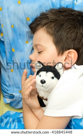 Cute little boy sleep and hugging his toy dog - stock photo