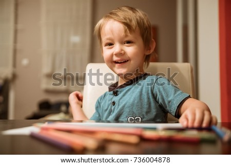 Cute Little Boy Smiling And Drawing With Pencils
