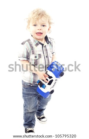 Cute little boy smiling and playing with police car against white background - stock photo