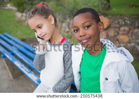 Cute little boy smiling at camera while friend talks on phone in the park