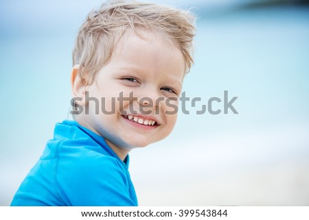 Cute little boy smiling on the beach - stock photo