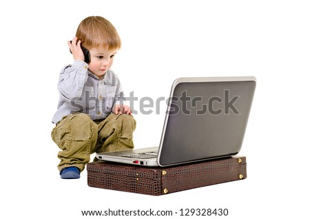 Cute little boy speaks on a mobile phone looking at laptop - stock photo