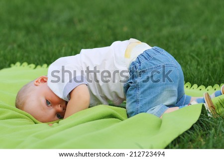 Cute little boy stand on his head and looking at camera - stock photo