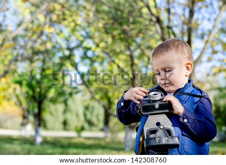 Cute little boy standing in a garden with trees playing with a vintage camera with copyspace - stock photo