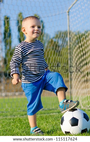 Cute little boy standing with his foot on his soccer ball and a look of anticipation as he waits for someone to play with him - stock photo
