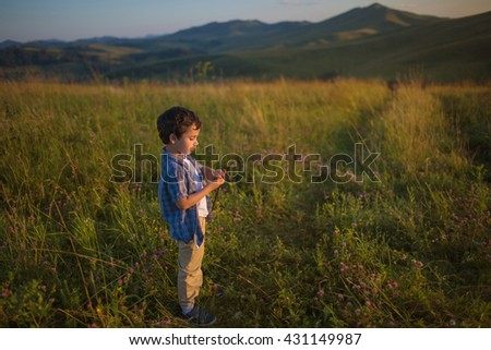 Cute little boy stands on a field at the sunset