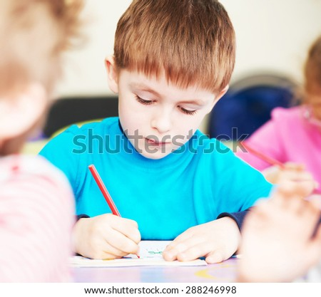 Cute little boy studying writing at the classroom - stock photo