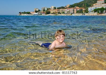 cute little boy swimming in the ocean near the coast - stock photo