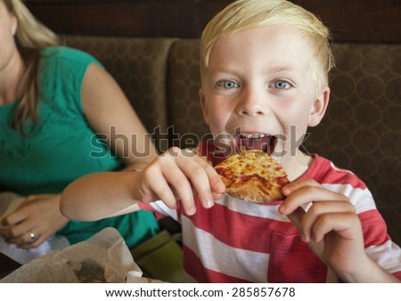 Cute little boy taking a big bite of cheese pizza at a restaurant - stock photo