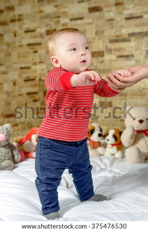 Cute little boy taking his first steps as he learns to walk with the aid of a helping hand from a parent, close up upper body