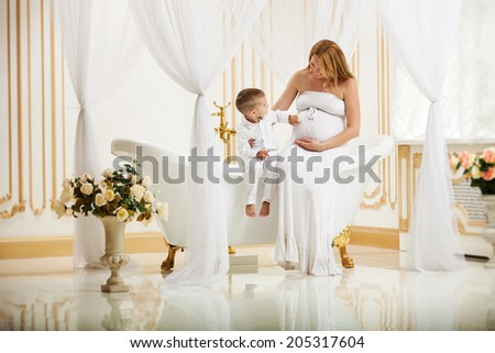 Cute little boy touching his pregnant mother's belly while sitting together on bathtub at home