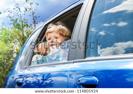 cute little boy traveling in the car and observing nature from open window - stock photo