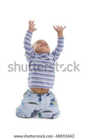 cute little boy trying to catch something coming from the top, isolated on white background