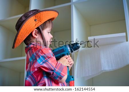 Cute little boy using an electric screwdriver - stock photo