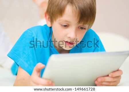 cute little boy using tablet computer - stock photo