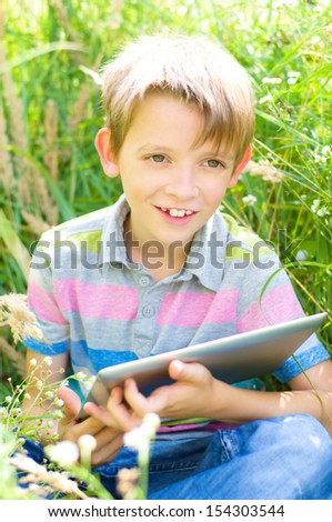 cute little boy using tablet computer outdoors - stock photo