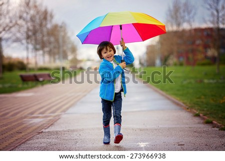Cute little boy, walking in a park on a rainy day, playing and jumping, smiling, springtime - stock photo