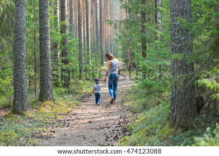 Cute little boy walking in park holding parents hand. Happy family and lifestyle concept