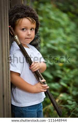 cute little boy wearing a coonskin cap and holding a toy rifle - stock photo