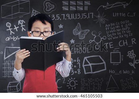 Cute little boy wearing glasses and standing in the classroom while reading a book with doodles on the chalkboard