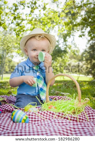 Cute Little Boy Wearing Hat Enjoying His Easter Eggs on Picnic Blanket Outside in the Park. - stock photo