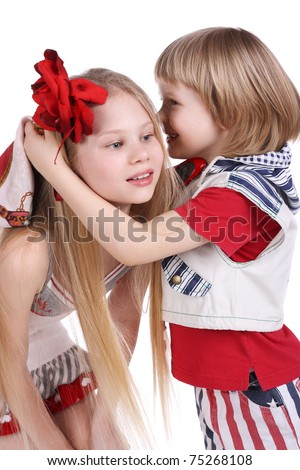 cute little boy whispering something to his beautiful sister - stock photo