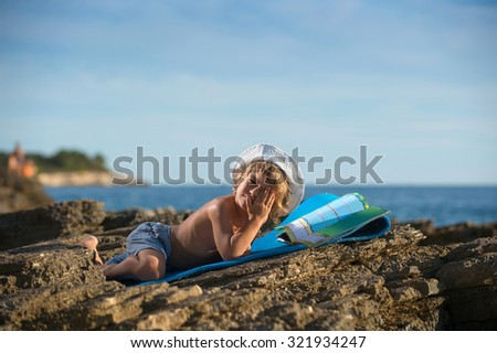Cute little boy with a cap lying on his stomach looking at his picture book on the beach. Some negative space around.