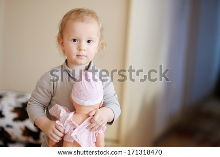 Cute little boy with a doll at home - stock photo