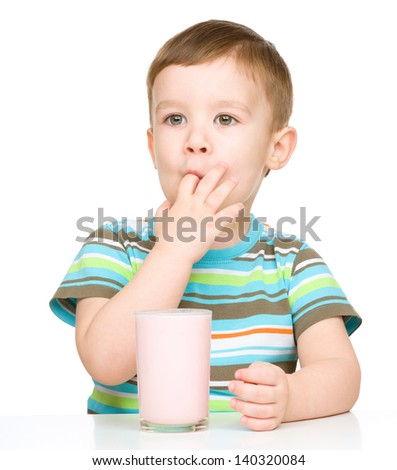 Cute little boy with a glass of milk sucking his finger, isolated over white - stock photo