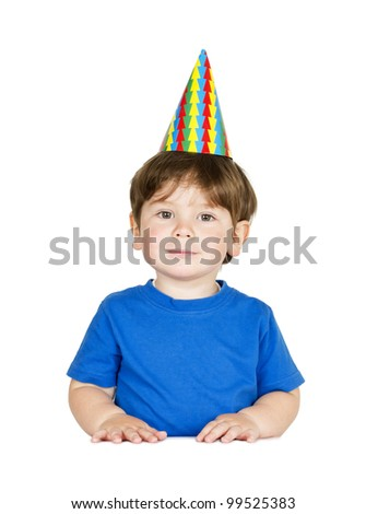 Cute little boy with a party hat at the table. Isolated on white.