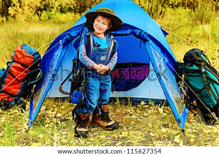 Cute little boy with backpack and tent outdoor.