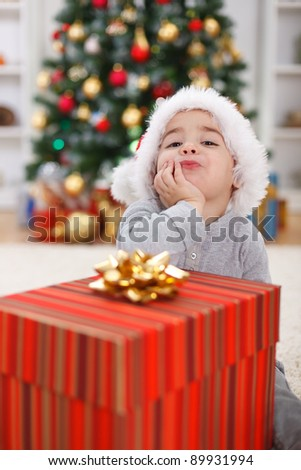 Cute little boy with big present, sitting in front of Christmas tree - stock photo