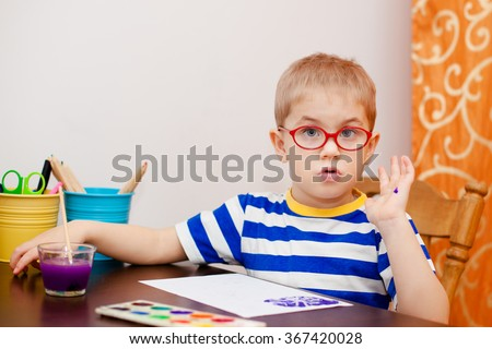 Cute little boy with blonde hair, blue eyes and glasses painting with brush and watercolors - stock photo