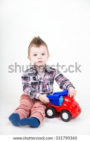 Cute little boy with blue eyes playing with a toy car. Happy kid sitting isolated on white background.