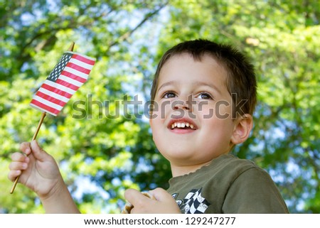 Cute little boy with brown hair and brown eyes waving an American flag while watching a parade