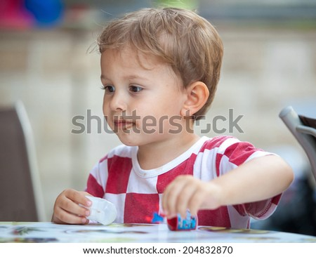 Cute little boy with chocolate smudges on face wearing Croatian jersey shirt and playing with toys. - stock photo