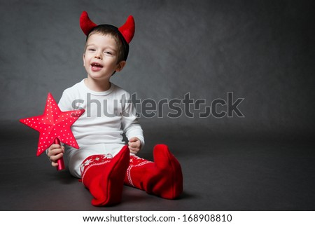 cute little boy with devil horns and red star, gray background - stock photo