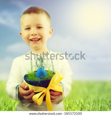 Cute little boy with Easter egg on the meadow. - stock photo