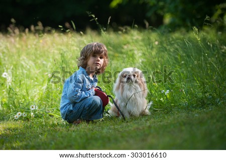 Cute little boy with his dog in the nature - stock photo
