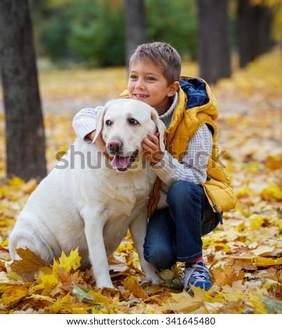 Cute little boy with his dog labrador retrievers outdoor in autumn beautiful park