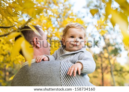 cute little boy with his father in the autumn park - stock photo